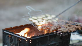 Turning round meat on the grill stock footage