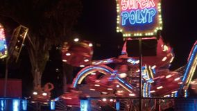 The turning roundabout at night in an amusement park. Amusement park at night. Flashing lights stock footage