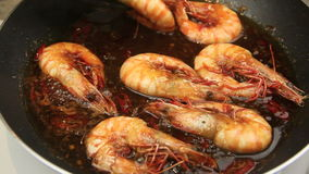 Turning Sizzling Prawns Tongs. Whole shrimps sizzling in a chili marinade being turned with tongs in a fry pan stock video footage