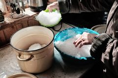 Turning Snow Into Water. A woman turning snow into a drinkable water at her kitchen, indoor shot royalty free stock photo