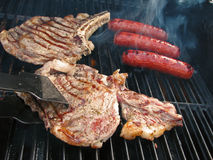 Turning Steak on the Grill stock photography