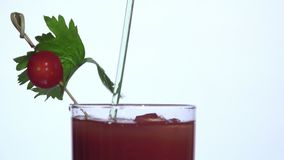 Turning stirrer stick on bloody mary. Closeup with white background,cocktail stick with tomato stock video