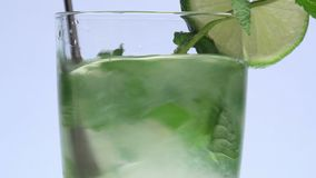Turning stirrer stick in a mojito. Closeup with white background, ice, lemon, rum stock video footage