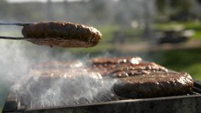 Turning tasty cutlets at grill close up stock photography