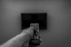 Turning on the television. A black and white shot of a person's hand pressing the television's remote control Royalty Free Stock Photography