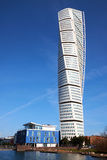 Turning torso rising over an apartment building. MALMO, SWEDEN - MARTS 28, 2014: Turning Torso tower building standing next to a small apartment building in West Stock Image