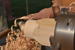 Turning a wooden figure. Royalty Free Stock Photo
