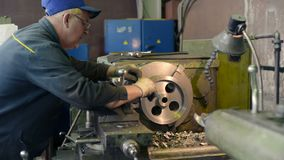 Turning works. The turner makes a metal part on a mechanical lathe. LIPETSK, RUSSIA - JUNE 15, 2017: Lipetsk Machine Tool Plant, Turning works. The turner makes stock video footage