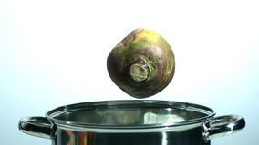 Turnip falling in a pot. In slow motion stock footage