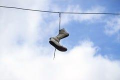 Turnschuhe, die an den Drähten auf einem Hintergrund des blauen Himmels hängen Lizenzfreies Stockbild