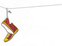 Turnschuhe, die am Draht auf weißem Hintergrund hängen Lizenzfreies Stockbild