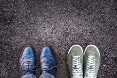 Turnschuhe und Geschäftsschuhe nebeneinander auf Asphalt, Arbeitslebenbalance Lizenzfreie Stockfotografie