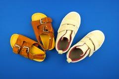 Turnschuhe und Sandalen auf einem blauen Hintergrund, Draufsicht, Sommerschuhe stockfotografie