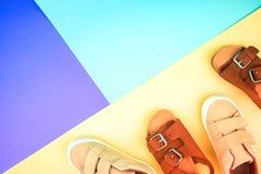 Turnschuhe und Sandalen auf einem modischen Farbhintergrund, Draufsicht, Sommerschuhe stockfotografie