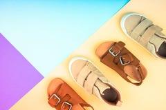 Turnschuhe und Sandalen auf einem modischen Farbhintergrund, Draufsicht, Sommerschuhe lizenzfreie stockbilder