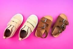 Turnschuhe und Sandalen auf einem modischen rosa Farbhintergrund, Draufsicht, Sommerschuhe lizenzfreies stockfoto