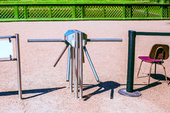 Turnstile and chair outdoors. In sunny day Stock Images