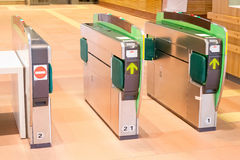 Turnstiles in underground railway station. Green arrows pointing to the way forwards. green barriers preventing progress Royalty Free Stock Images