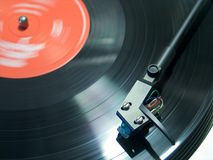 Turntable 1. View from top. Red label on record. Focus on the arm and light spot at the same place stock images