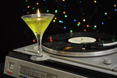 Turntable with a candle. Spinning turntable with a fancy wineglass candle against colorful lights on a black background Stock Photo