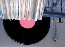 Turntable in gray case and row of many close standing vinyl records in old color covers on a desk top view Royalty Free Stock Image