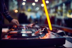 Turntable, hand of dj on the vinyl record at night club. blured background royalty free stock image