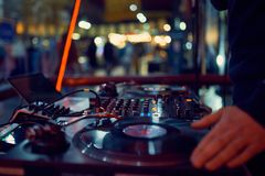 Turntable, hand of dj on the vinyl record at night club. blured background stock photography
