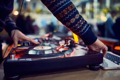 Turntable, hand of dj on the vinyl record at night club. blured background stock photo