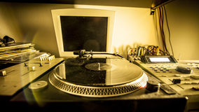 Turntable in home recording studio. Illuminated by a yellow light Stock Images