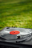 Turntable with LP vinyl record against green background Stock Photos