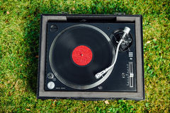 Turntable with LP vinyl record on grass background Stock Photo
