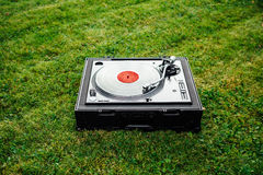 Turntable with LP vinyl record on grass background Stock Image