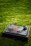 Turntable with LP vinyl record on grass background Royalty Free Stock Photo
