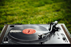Turntable with LP vinyl record on grass background Royalty Free Stock Images