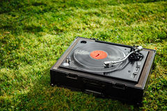 Turntable with LP vinyl record on grass background Royalty Free Stock Photography