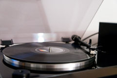 Vinyl record on turntable. Long playing vinyl record on turntable of gramophone with closeup view of needle, loudspeaker and plastic lid Royalty Free Stock Images