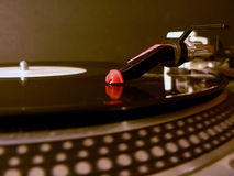 Turntable needle on record 2. Photo of dj turntable needle on record with the focus on the needle illuminated under party lights royalty free stock photo