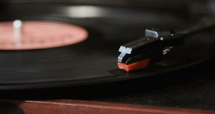 Close-up of using an antiquarian vinyl record player. turntable player,dropping stylus needle on vinyl record playing. Turntable player,dropping stylus needle on stock video