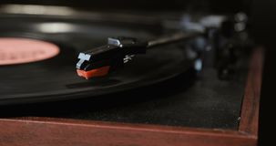 Close-up of using an antiquarian vinyl record player. turntable player,dropping stylus needle on vinyl record playing. Turntable player,dropping stylus needle on stock footage