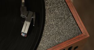 Close-up of using an antiquarian vinyl record player. turntable player,dropping stylus needle on vinyl record playing. Turntable player,dropping stylus needle on stock video footage
