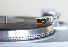 Turntable is playing disk. The stylish 20-years old turntable is playing disk. The tone-arm cartridge is in focus. You can put your logo, signs and text on it Royalty Free Stock Images