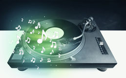 Turntable playing music with audio notes glowing Royalty Free Stock Image
