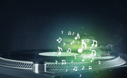 Turntable playing music with audio notes glowing Royalty Free Stock Images