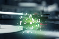 Turntable playing music with audio notes glowing Royalty Free Stock Photo