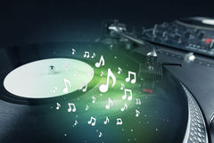 Turntable playing music with audio notes glowing Stock Photography