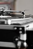 Turntable playing vinyl audio record. Professional analog djing equipment playing the music Royalty Free Stock Image