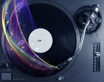 Turntable playing vinyl with glowing abstract lines Royalty Free Stock Photos