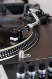 Turntable playing vinyl music record. Macro of tonearm with needle scratching the 78 rpm disc Royalty Free Stock Photos
