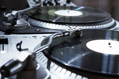 Turntable playing vinyl record with music. Professional sound equipment for a disc jockey. Turntable vinyl record players and 2 channel sound mixing controller Royalty Free Stock Image