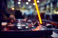 Turntable, ręka dj na winylowym rejestrze przy noc klubem blured tło obraz royalty free